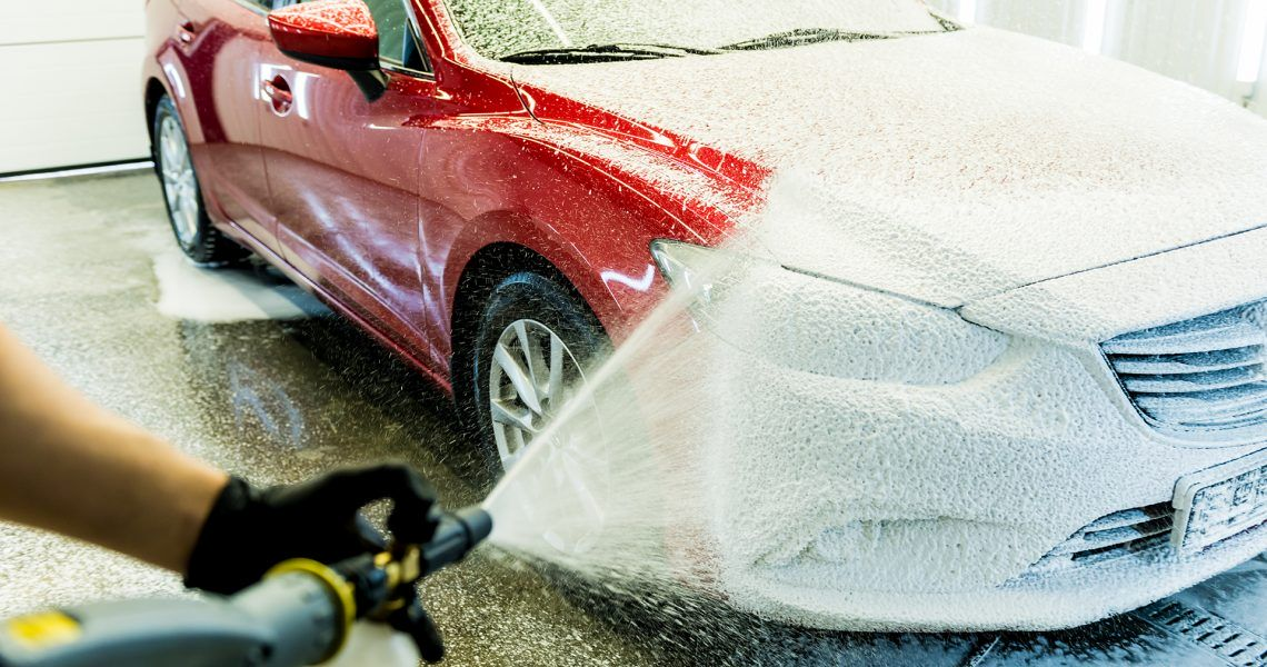 Worker washing car with active foam on a car wash